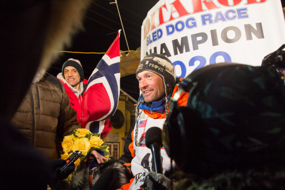 A picture of Thomas Waerner in front of the Iditarod finish sign and a Norwegian flag in Nome, Alaska.